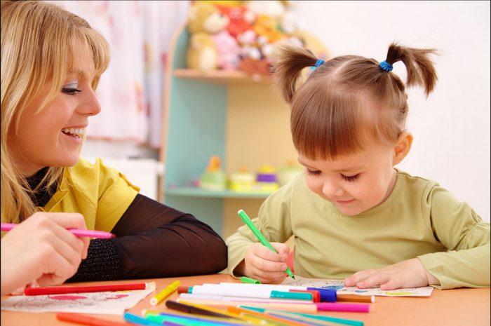 няня учит девочку рисовать