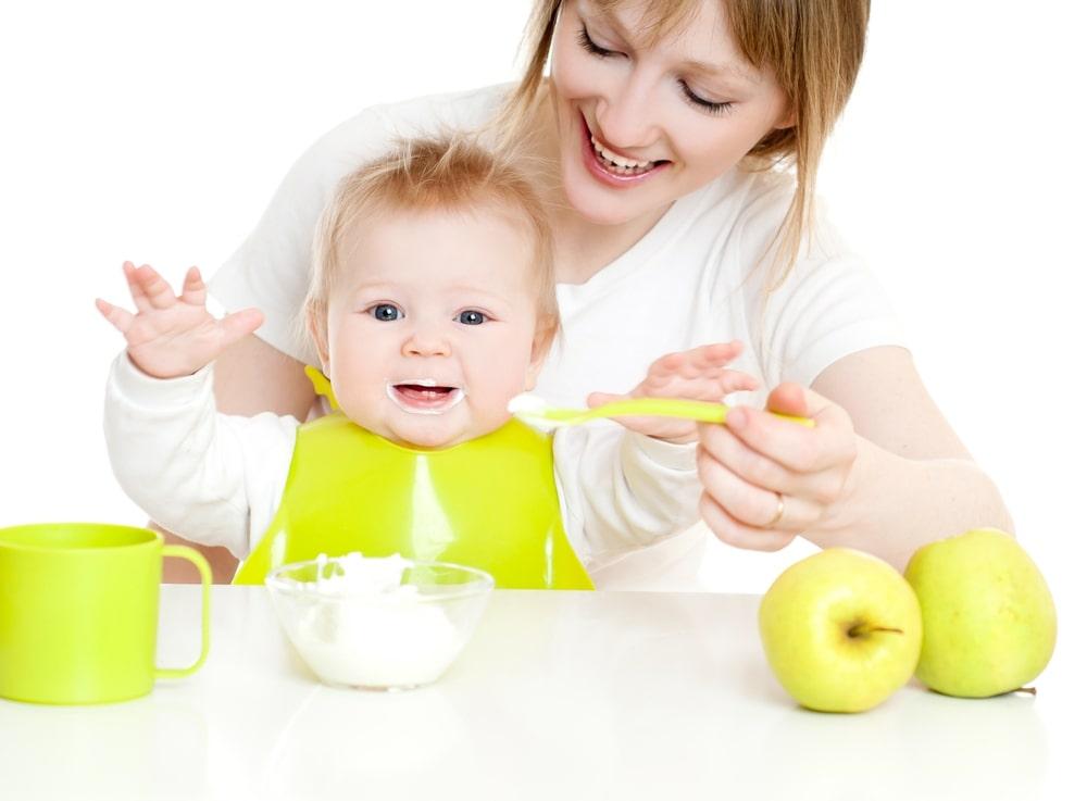 няня кормит малыша